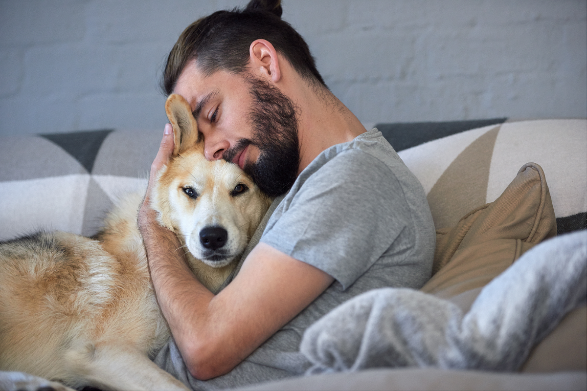 A photo of a man faced with rehoming a dog, snuggling with it.